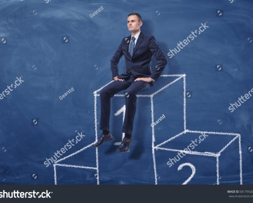stock-photo-businessman-is-sitting-on-the-first-place-of-a-podium-on-blue-blackboard-background-succes-581799202